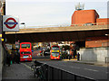 The entrance to Westbourne Park Underground station is on the immediate left. Beyond that the road crosses the Great Western main line before passing under the A40(M) Westway. The orange building, partly under Westway, is Westbourne Park bus garage.