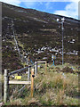 NN7088 : Wind-powered electric fence rising on heather slope by Trevor Littlewood