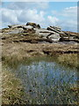 SK0689 : Small tarn and rocky area by Andrew Hill