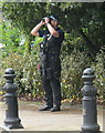TQ2777 : Diamond Jubilee Pageant - armed policeman scans rooftops with binoculars by David Hawgood