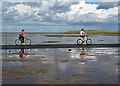 NU0943 : Cyclists on Lindisfarne Causeway by Walter Baxter