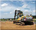 TG1715 : Digger parked beside Reepham Road by Evelyn Simak