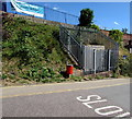Located in the bank below the village railway station on the Avocet Line. The substation identifier is LYMPSTONE STATION 5105. The banner on the station perimeter railings shows MORE TRAINS EVERY SUNDAY. The red bin is for dog waste.