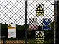 TL1780 : Signs on gate to mobile telephone mast buildings by Andrew Tatlow