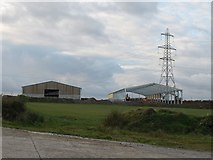 SW9963 : Barns and pylon by Derek Harper