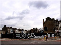 TQ2775 : Painted fence on St John's Hill where once stood a pub named The Plough by tristan forward