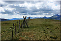 SH6954 : A stile with a mountainous skyline by Ian Greig