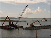 SZ3394 : Lymington: breakwater building and ferry approaching by Chris Downer