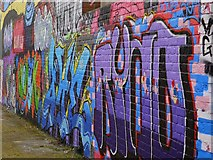 NZ2563 : Graffiti Wall on Maiden's Walk by Andrew Curtis