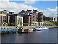 NZ2564 : Flow tidemill artwork and river cruise boats moored on the Tyne by Graham Robson