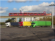 TQ4180 : Car park, colourful lorries and a DLR train by Gareth James