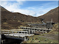 NH1737 : Bridge, pipeline and dam in Gleann Innis an Loichel by Trevor Littlewood