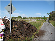 L9034 : Peat stack and road by Jonathan Wilkins