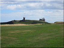 NU2422 : Looking across the golf course towards Dunstanburgh Castle by Graham Robson