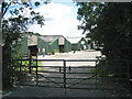 SP1369 : Dark green sheds at Hill Farm by Robin Stott