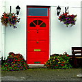 M2208 : Ballyvaghan B&B - White Wall  & Red Door with Lanterns & Flowers at Both Sides by Joseph Mischyshyn