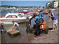 SX9372 : Examining a catch of sand eels, back beach, Teignmouth by Robin Stott