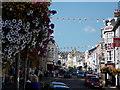SY3492 : Lyme Regis: bunting and flowers in Broad Street by Chris Downer