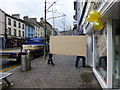 H4572 : Workmen with a large board in High Street Omagh by Kenneth  Allen