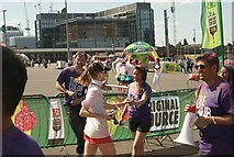 TQ1985 : View of a Colour Runner taking a bottle of water at the finish line by Robert Lamb