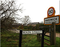 TL3758 : Main Street & Hardwick Village Name sign by Adrian Cable