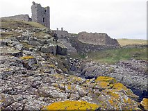 NU2521 : Dunstanburgh Castle above Queen Margaret's Cove by Andrew Curtis