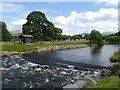 NY2523 : A Weir And Flood Defences On The Derwent by James T M Towill