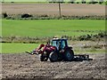 NZ0657 : Tractor with a disk harrow by Robert Graham