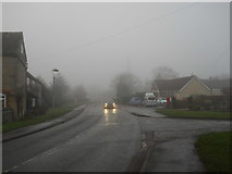 TF1505 : High Street, Glinton, on a foggy day by Paul Bryan