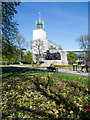 NZ2464 : Flower bed with bronze sculpture beyond by Trevor Littlewood