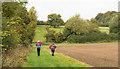 TL7551 : Walkers on field headland by Trevor Littlewood