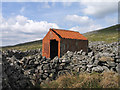 NY6734 : Corrugated metal building within stone walling by Trevor Littlewood