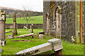 NS0567 : Inclined gravestones beside St. Colmac's Church by Trevor Littlewood