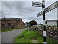NY6134 : Road signs and barn conversion in Ousby by Rob Purvis