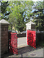 SP9211 : The Gates by the West Door of Tring Church have been covered with woollen poppies by Chris Reynolds