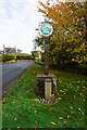 TG1216 : Attlebridge sign with WW1 memorial in front by Ian S