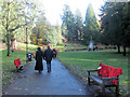 SP9211 : People walk, and remember, past the poppy-covered seats in Tring's Memorial Garden by Chris Reynolds