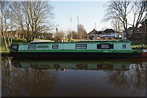 TQ1479 : View of a narrowboat reflected in the Grand Union Canal at Three Bridges by Robert Lamb
