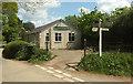 SS5626 : Signpost and village hall, Ensis by Derek Harper