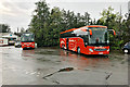 NT0805 : Two Orange Coaches outside Moffat Woollen Mill by David Dixon