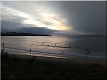 C8540 : Surfers at sunset West Bay Portrush by Willie Duffin