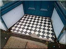 SH6266 : A damaged tiled shop doorway on the High Street, Bethesda by Meirion