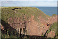 NO6641 : Red, coloured sandstone in a cliff exposure at Dickmont's Den by Andrew Diack