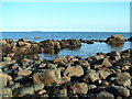 NO5904 : Rocks at low tide by James Allan