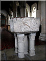 TF9507 : The church of All Saints - baptismal font by Evelyn Simak