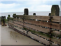 TG3533 : Wooden groyne and pebbles by Evelyn Simak